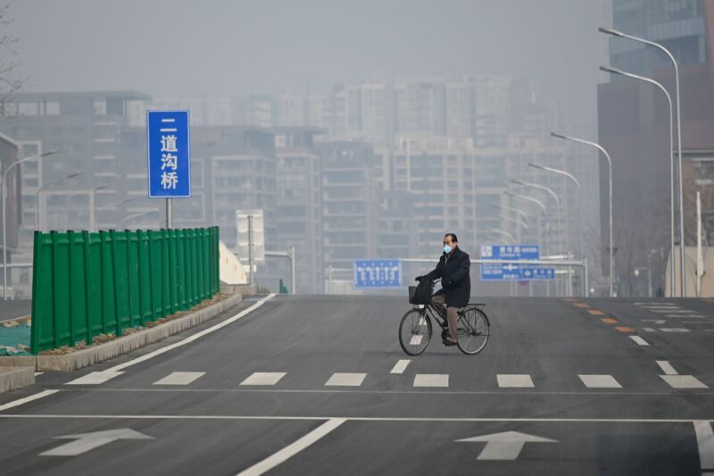 A man wearing a face mask rides his bicycle along an empty street in Beijing on February 12, 2020.